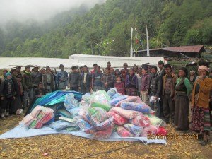 Villagers and workers with tarps, sleeping mats, blankets